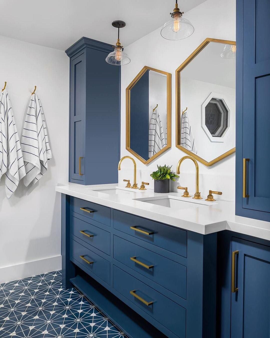 Bathroom With Navy Cabinets Marble Countertops And Gold Light Fixtures And Pulls Bathroom Renos Bathrooms Remodel Amazing Bathrooms