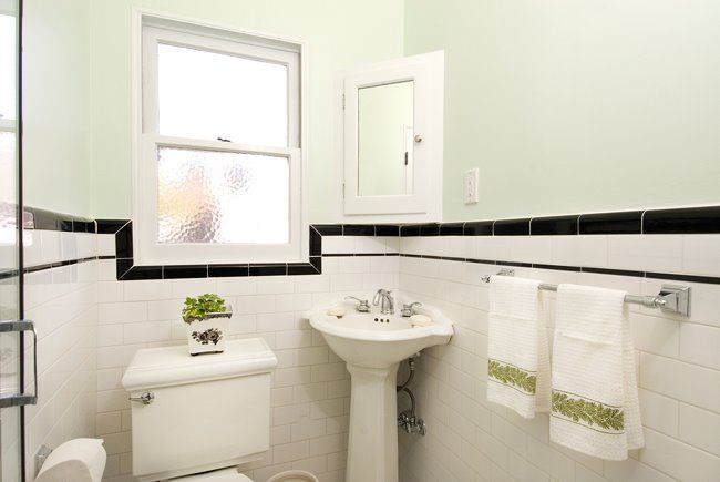 White subway tile bathroom with black border and interesting window