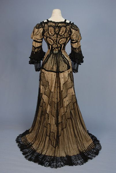 TRAINED BLACK LACE EVENING GOWN with SEQUINS, c. 1905. 2-piece dotted net with lace insertions and velvet trim over cream silk faille: Boned square neck front closing bodice with puffed shoulder, ruffled 3/4 sleeve decorated with sequins, velvet bands and shell pattern lace. Skirt with two wavy bands of floral lace, ruffled hem with velvet bands. - Back View