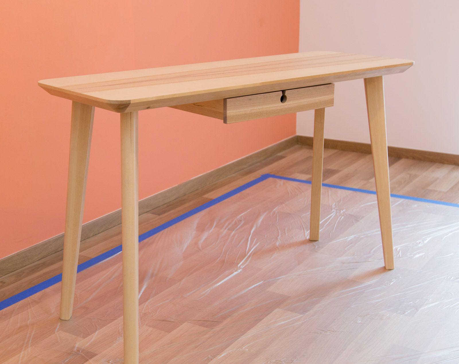 Pourquoi s'en tenir aux basiques, quand on peut customiser, décorer et adapter un meuble à ses envies décoratives? Prenez ce bureau de style suédois à la belle allure, mais manquant d'un petit peu de fantaisie. Choisissez une couleur de peinture contrastant bien avec la couleur principale de la pièce, ici du blanc pour un mur orange. La réussite dépendra surtout d'une application aux motifs nets et finitions parfaites. Le secret réside dans le ruban de masquage.