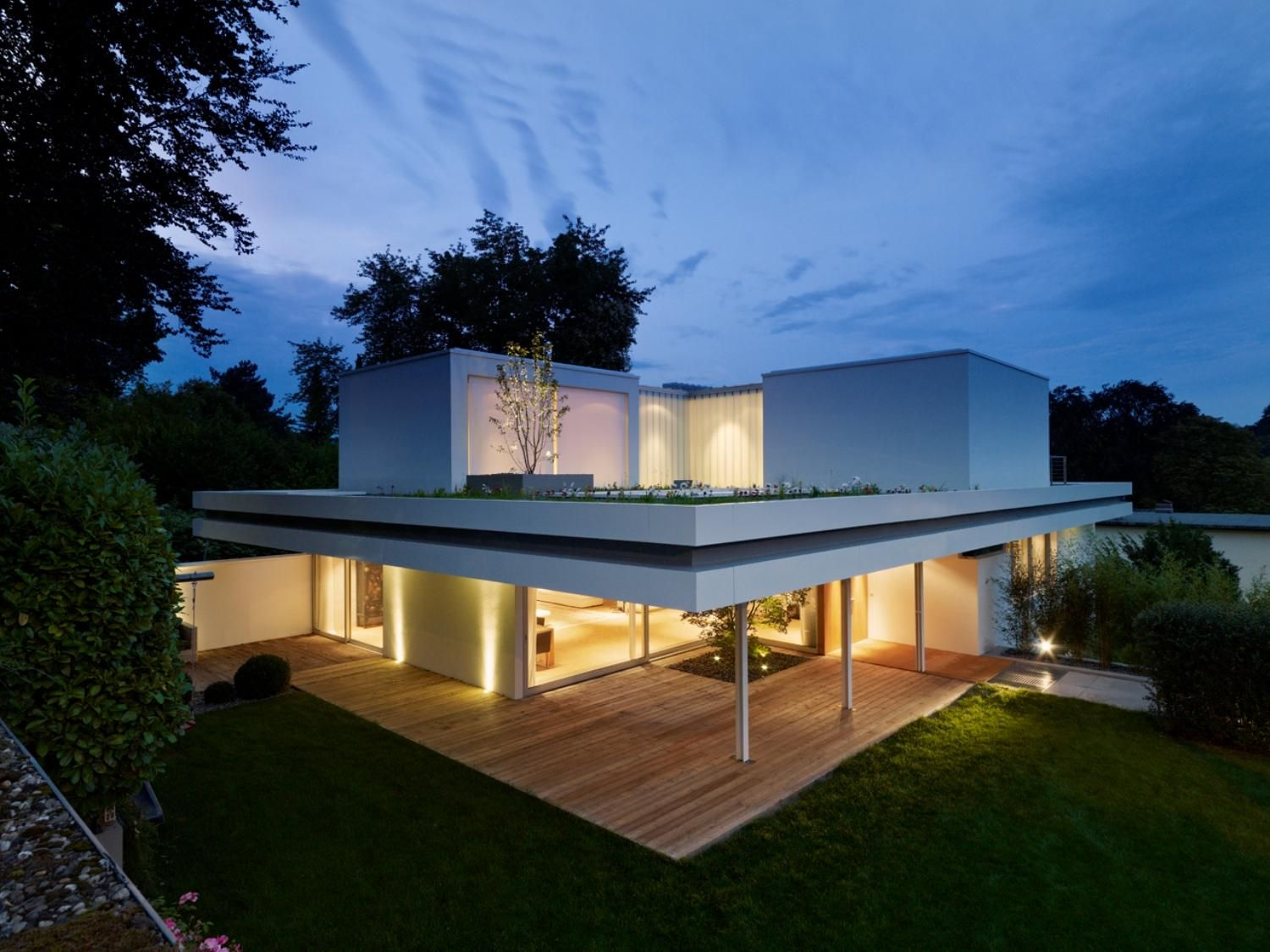 Three single boxes placed on a cantilevered flat roof, which are ...
