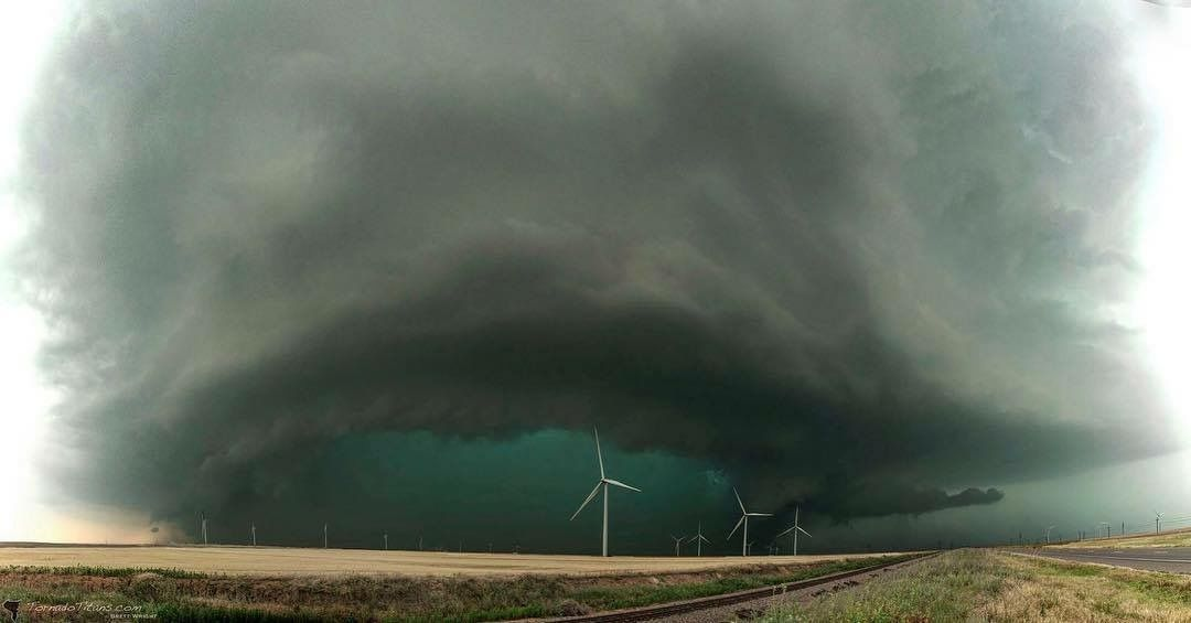 風力発電機を覆い隠すほど巨大な竜巻の画像