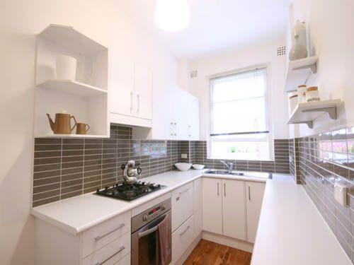 une jolie cuisine blanche avec une crédence grise, parquet au sol ...