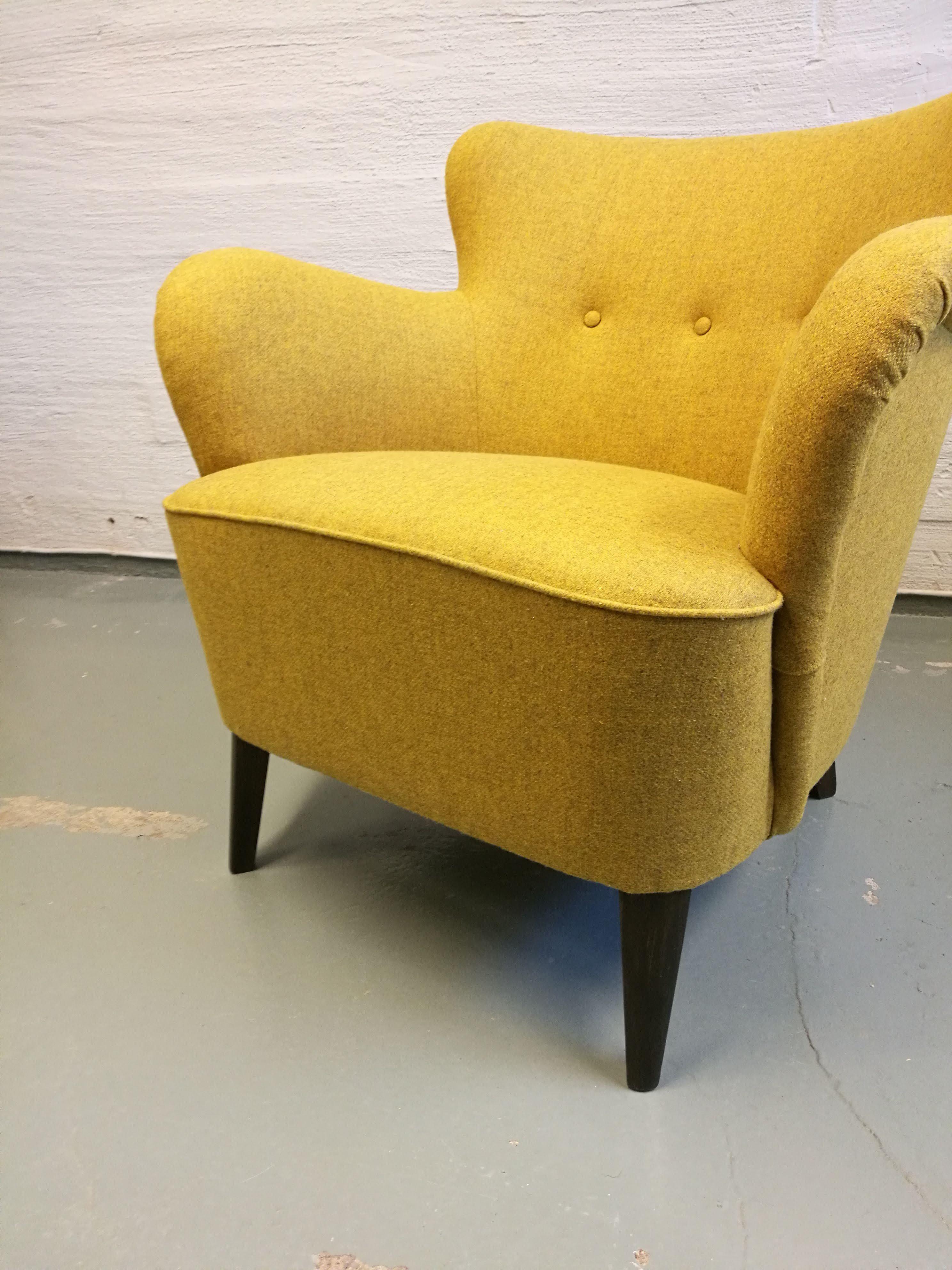 Keltaisella villakankaalla verhoiltu nojatuoli.   Nojatuoli