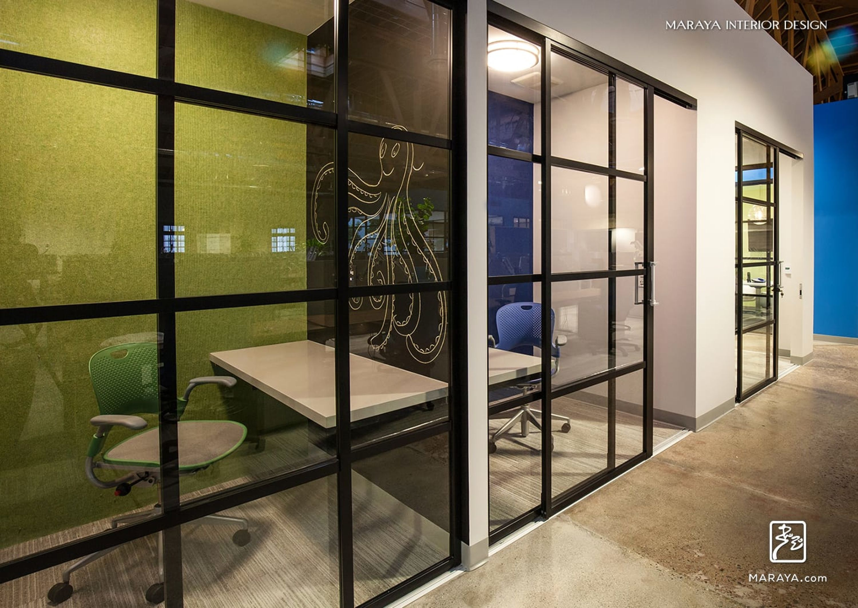 Modern open office com company phone rooms black sliding glass doors polished concrete floors maraya interior design