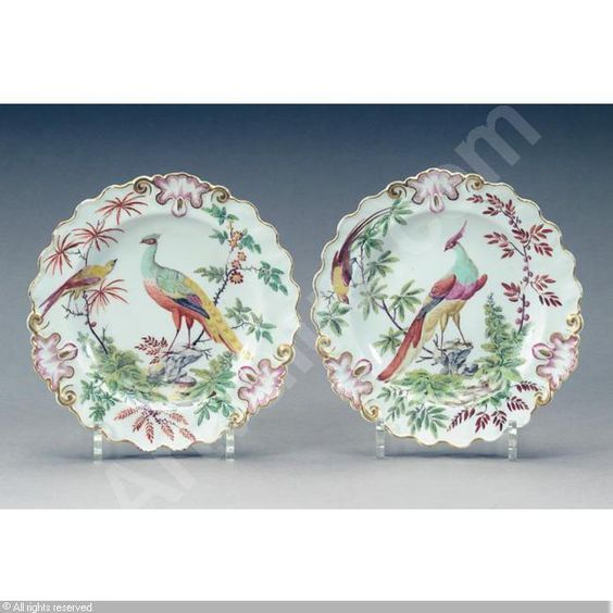 Chelsea plates, ca. 1760. A pair: painted with exotic birds perched in ornamental trees, gilt-edged shaped rims: