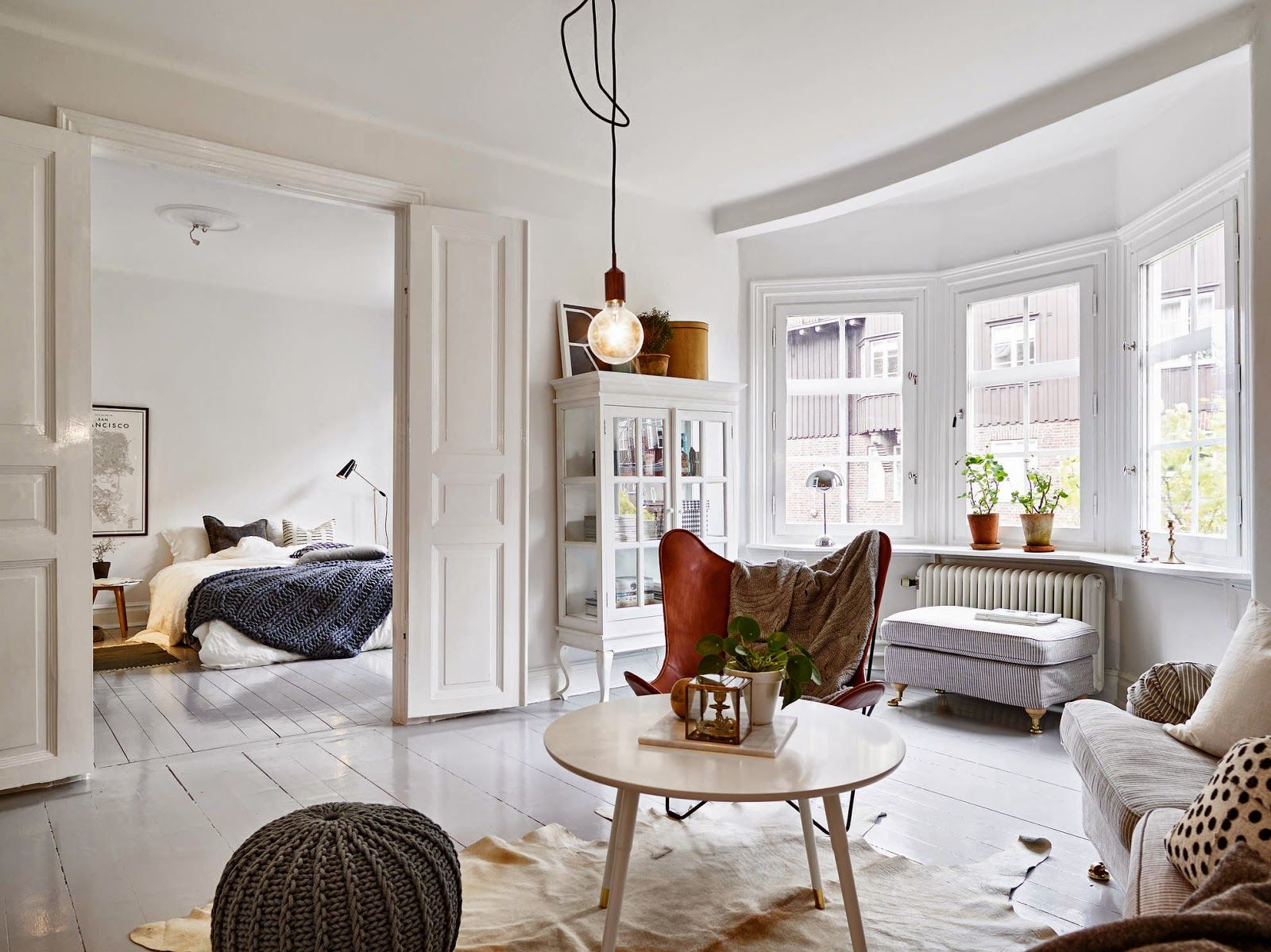 A swedish apartment with a cosy bed and glossy grey floor