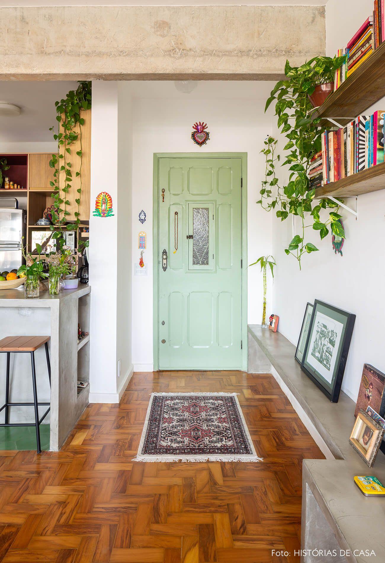 Apartamento colorido com clima étnico tem estruturas de concreto, porta de entrada pintada de verde e muitas plantas.  | A colorful apartment that looks like a house with indian, mexican and brazilian items, concrete and plants.