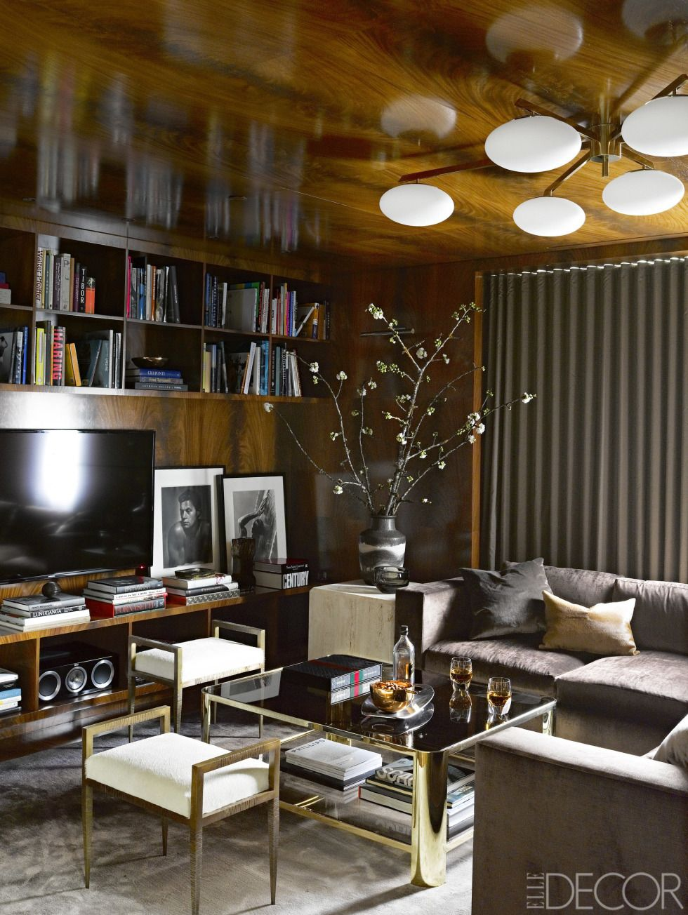 Sexy den.  Wood walls and ceiling.  Mid century chandelier.  Brass stools.  Grey velvet sectional.