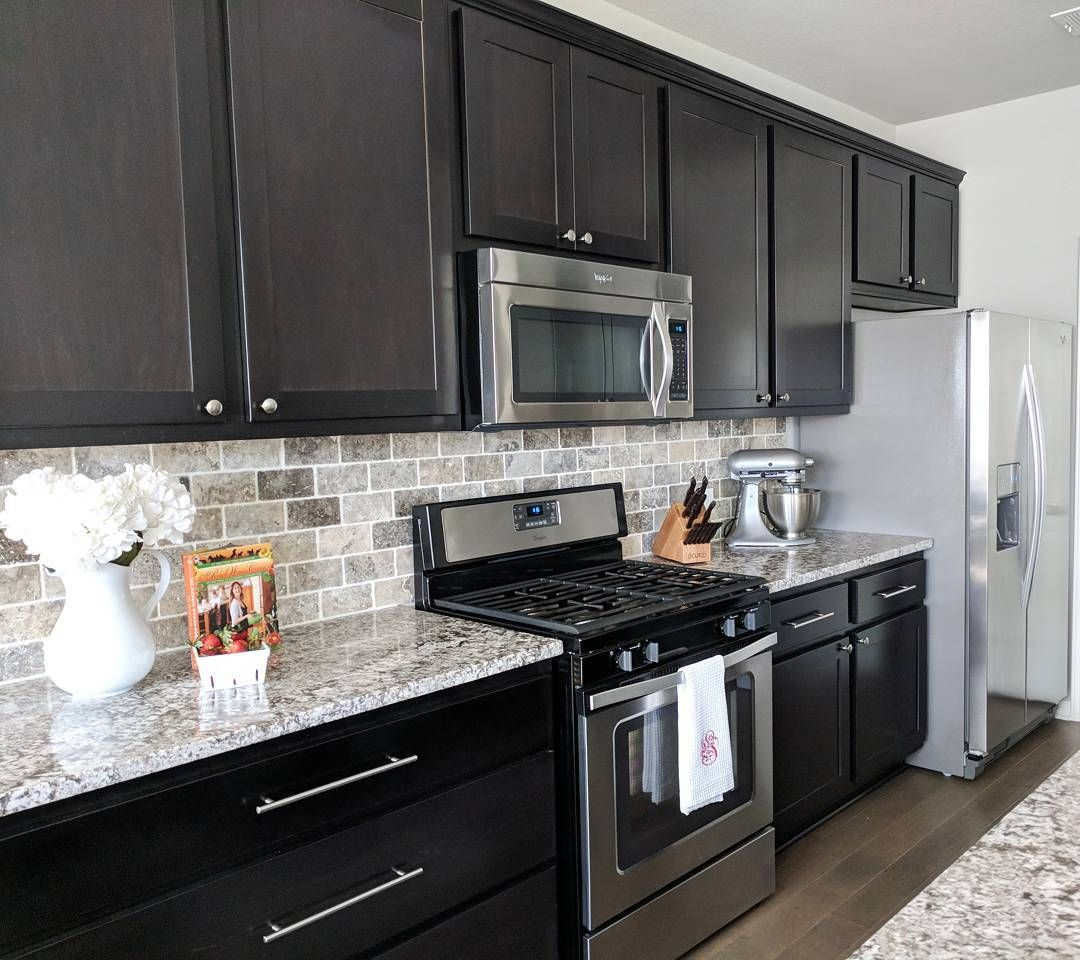 Dark Cabinets White And Gray Granite Countertops And Travertine
