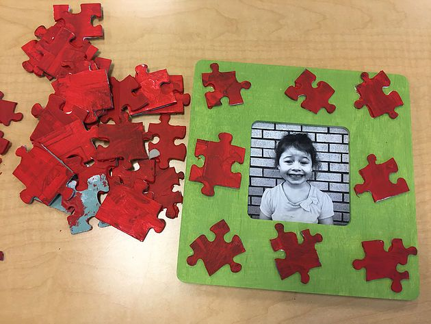 Preschool parent gift.  The children's black and white photos inside a wooden frame.  They painted the frame green and painted puzzle pieces red.