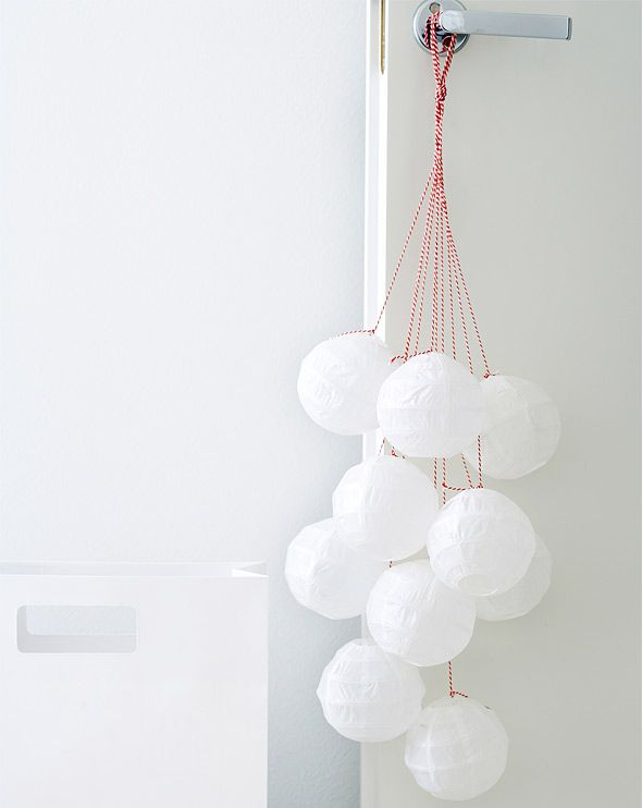 DIY door decoration idea: String paperballs from an old set of chasing lights or use Christmas tree balls to create a modern Christmas decoration.