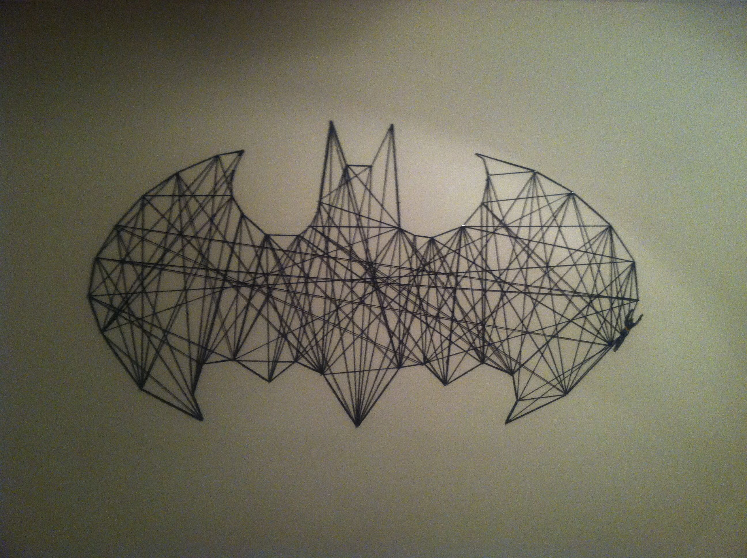 This is a bat symbol that I strung together using yarn and nails that were already in my wall.