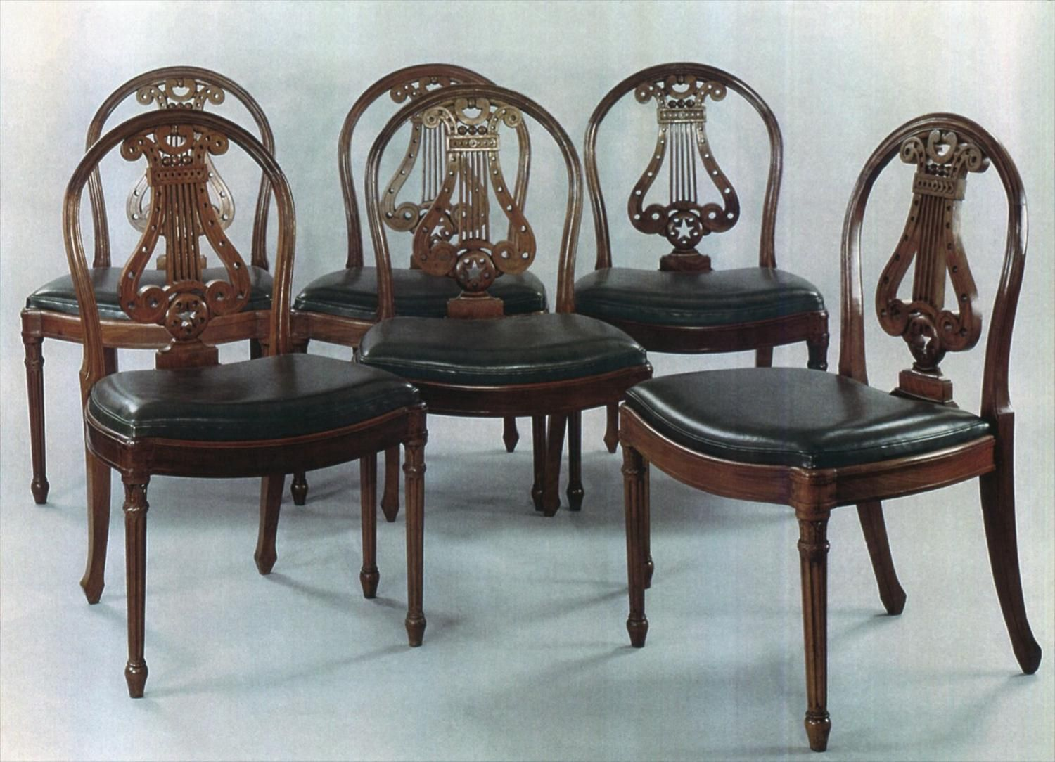date unspecified A SET OF SIX CARVED MAHOGANY CHAIRS. OPEN BACK IN THE FORM  OF A LYRE. RAISED ON FLUTTED TAPERING LEGS WITH SCULPTED LOTUS FLOWERS. - Date Unspecified A SET OF SIX CARVED MAHOGANY CHAIRS. OPEN BACK IN