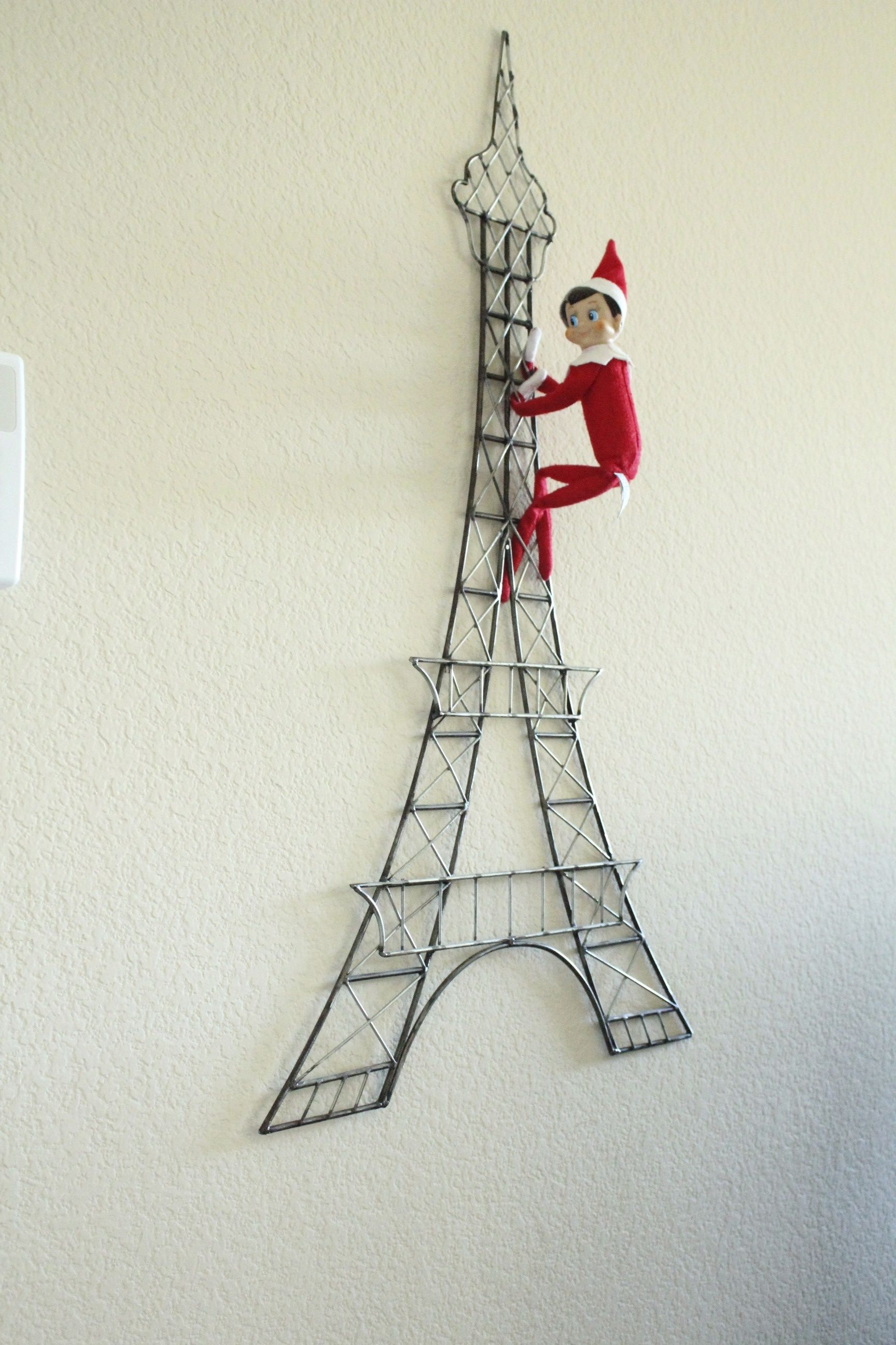 Elf on the shelf climbing eiffel tower