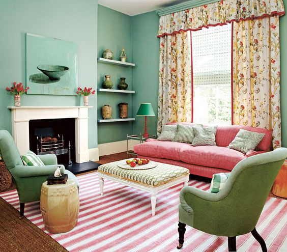 Furniture arrangement not centered on fireplace, mint green living room with pink decor, nice textile patten mix, striped rug, solid chairs, large gingham pillows, trellis ottoman, floral drapes, subtle stripe sofa, small geometric pillows