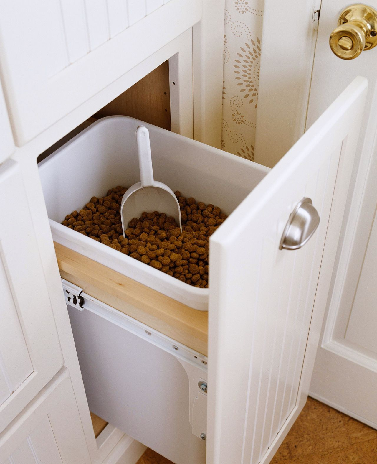 Large dogs typically require a lot of food and finding a convenient way to store dog food can be tricky. To make feeding time easier, outfit a pull-out cabinet with a bin of ready-to-scoop kibble. #petstorageideas #storageandorganizationideas #petsuppliesorganization #dog #cat #petparent #bhg