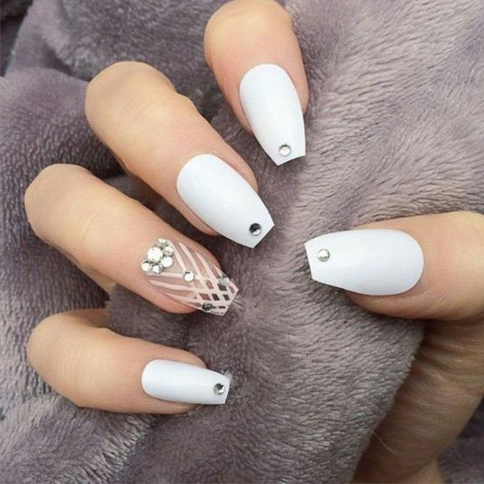 long square fingernails, four painted white and decorated with ...