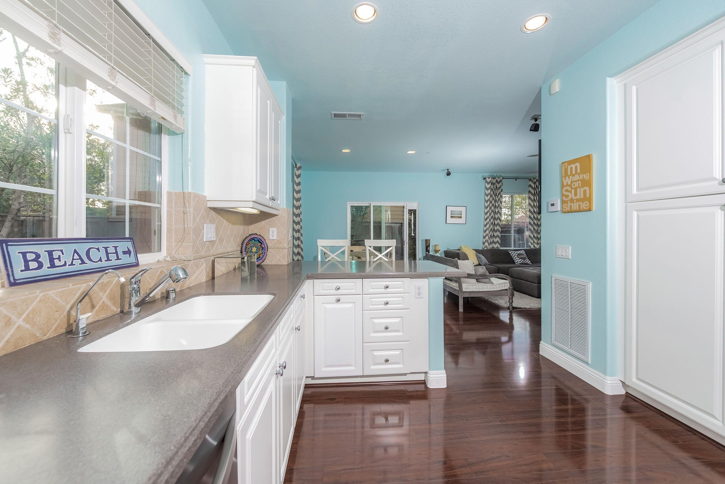 The open kitchen features Corian countertops, custom backsplash ...