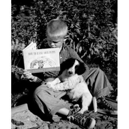 Boy sitting with dog and reading book Canvas Art - (24 x 36)