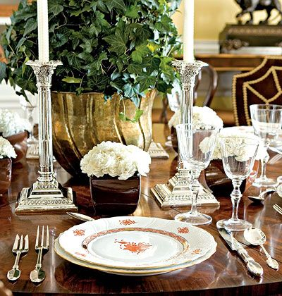 A large topiary centerpiece combined with individual bud vases gives this simple china table setting a casual glamour.