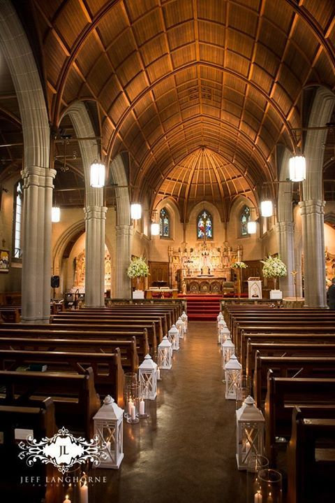 White lanterns light the way down a church aisle  Red floral architecture  Wedding Design