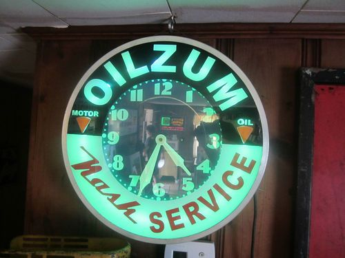 Neon clock advertising OILZUM and Nash Services
