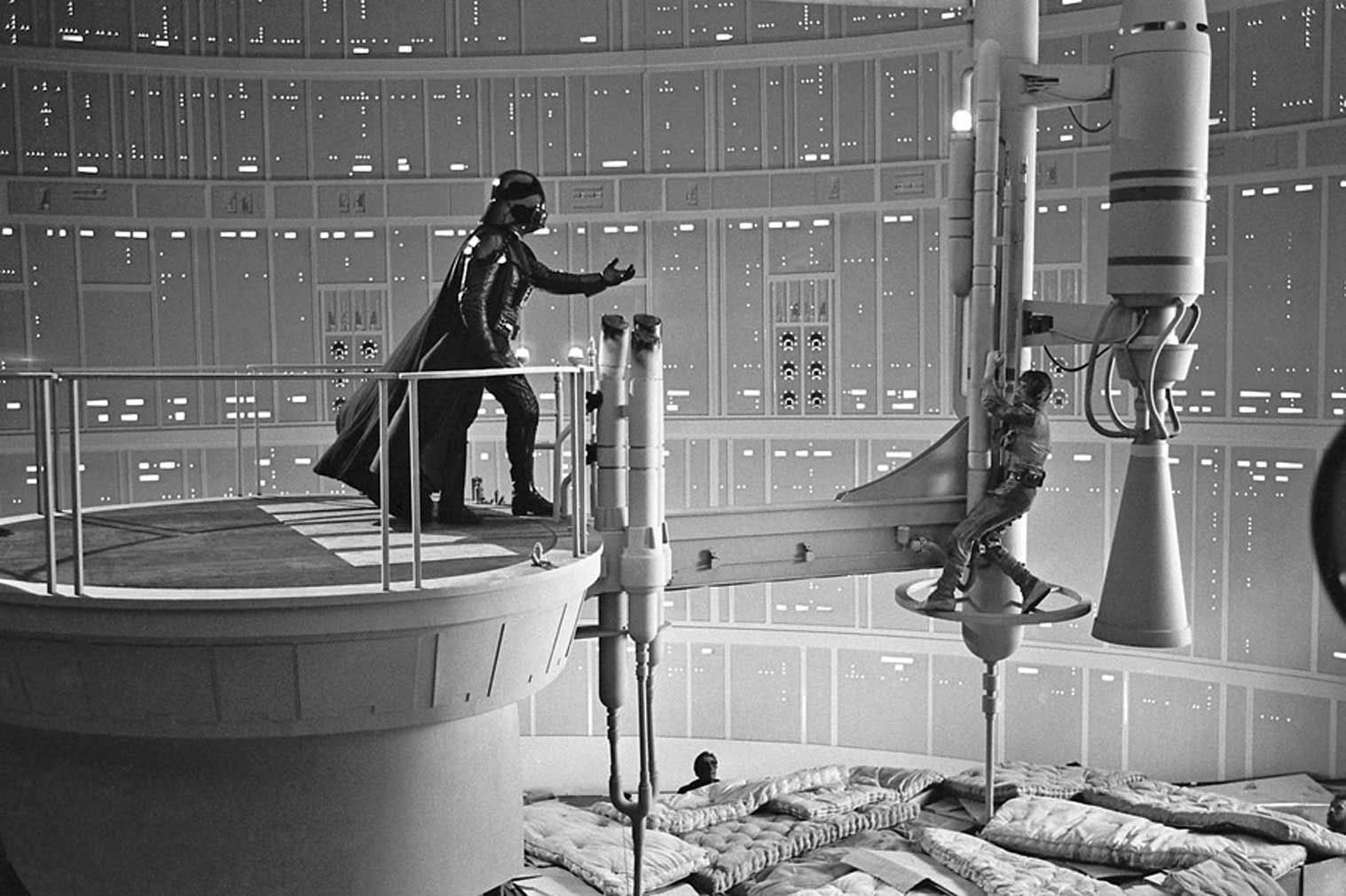 David Prowse and Mark Hamill filming the classic scene in The Empire Strikes Back above a bunch of mattresses and cardboard boxes.