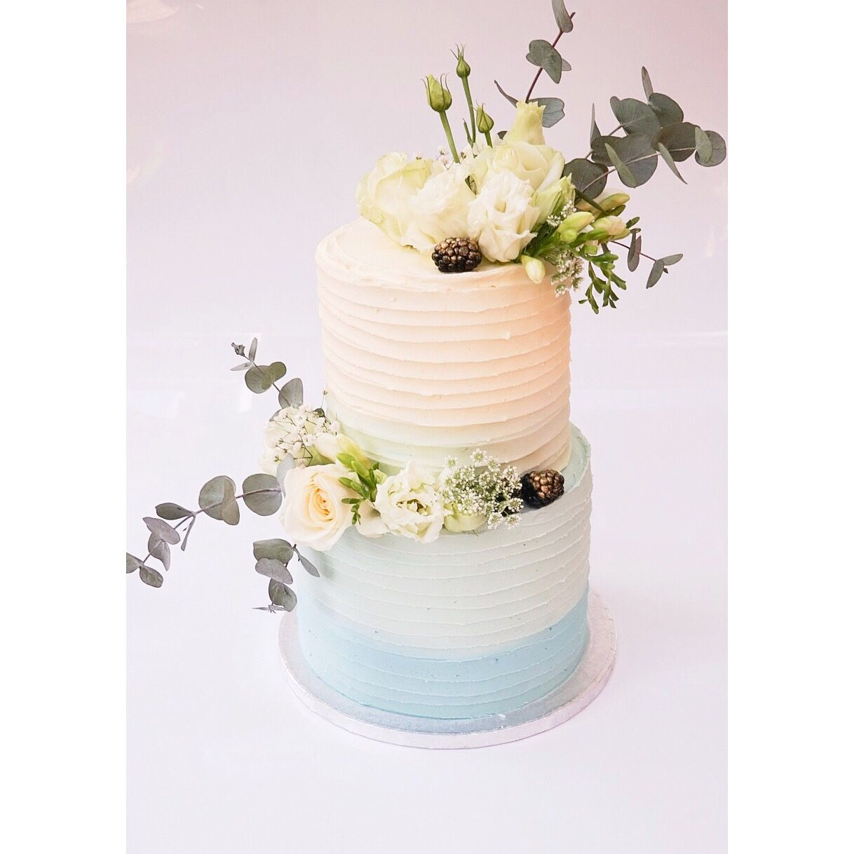 Two tier christening cake decorated with fresh flowers and