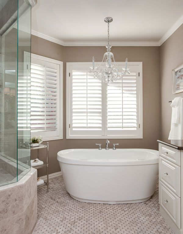 Freestanding soaking tub with chandelier lighting above in greenwood village bathroom remodels for Bathroom remodel greenwood in