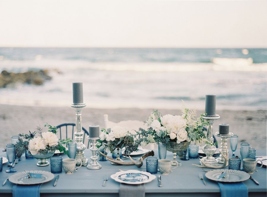 Beach wedding inspiration: Reception tabletop by the sea designed in a palette of ocean blues. Image by Melanie Gabrielle. Design and styling by Ever After Event & Floral Design and Love in Vintage. Florals by Ever After Event & Floral Design. www.weddingsunveiledmagazine.com