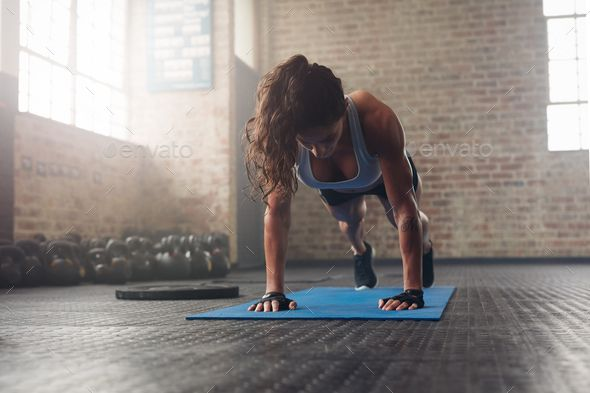 Young muscular woman doing core exercise by jacoblund. Young muscular woman doing core exercise on f...