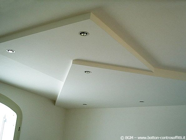 Controsoffitto con volumi ad incastro a 45° e faretti. soffitto