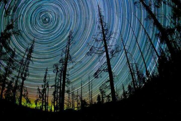 "Seeing Stars Spin This gorgeous image required an all-night exposure, made on a night with no moon and clear skies. It was shot on Blackcomb Mountain in British Columbia, Canada. The photographer, Kim Eijdenberg, told National Geographic's My Shot, ""It's amazing to think it's really us who are spinning in relation to the stars."" That's because the Earth rotates on its axis and revolves around the sun."