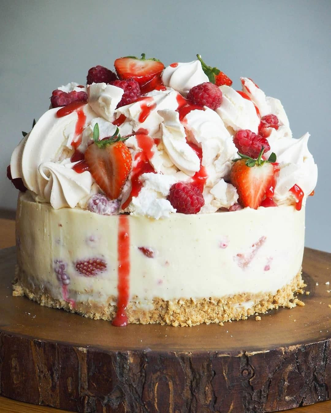 White Chocolate Cheesecake folded with Strawberries & Raspberries on a classic digestive base. Topped with a mountain of eton mess; crush meringues, fresh meringues and fresh berries #chocolatecheesecake #whitechocolateraspberrycheesecake
