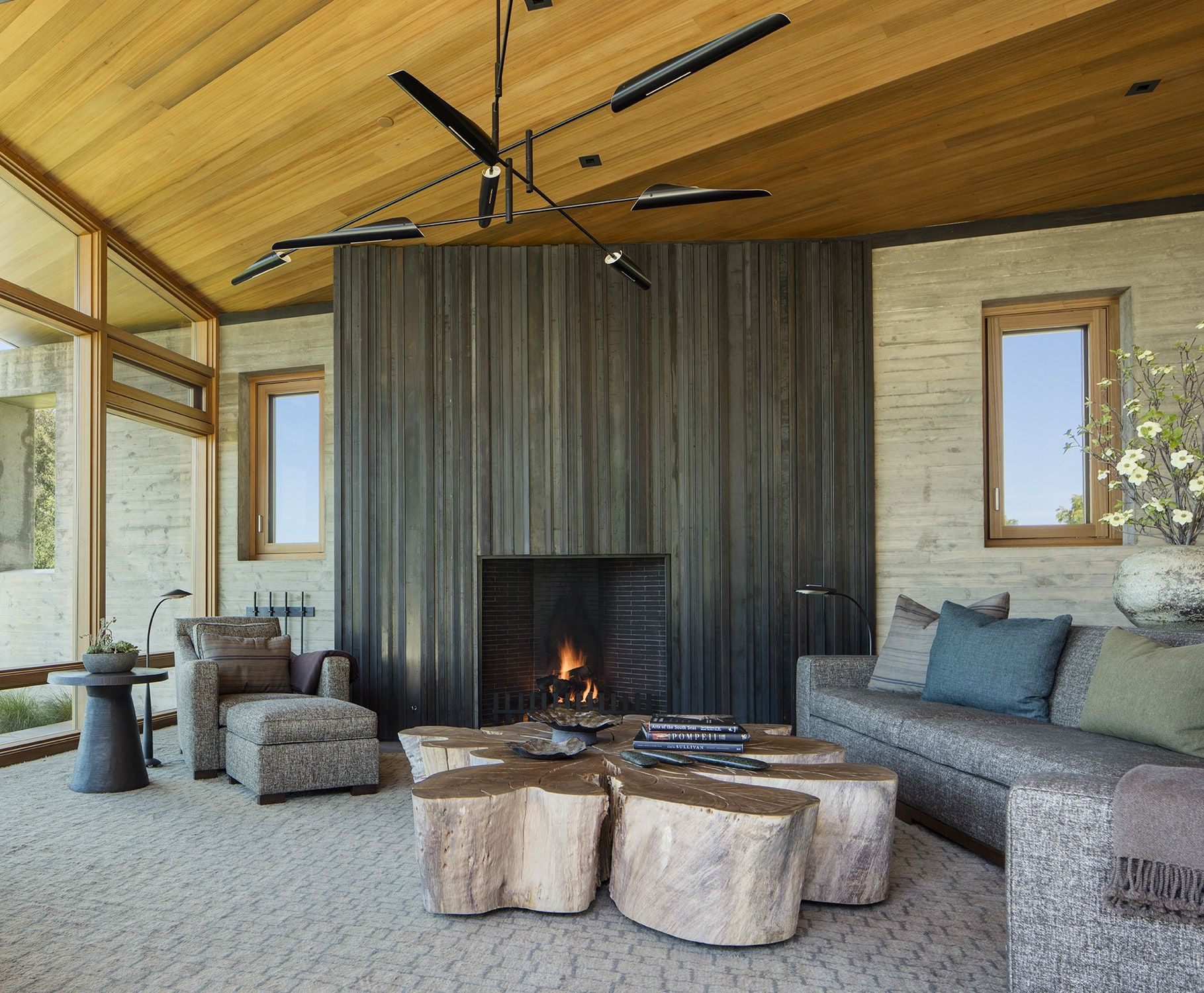 Modern living room concrete and wood grand fireplace eucalyptus coffee table
