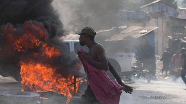 A protester walks by burning tires placed by demonstrators demanding the resignation of Haiti's President Michel Martelly and Prime Minister Laurent Lamothe in Port-au-Prince, Haiti, Friday, Dec. 12, 2014. The protest occurred hours before Martelly was scheduled to talk about a commission report that calls for a new consensus government. (AP Photo/Dieu Nalio Chery)