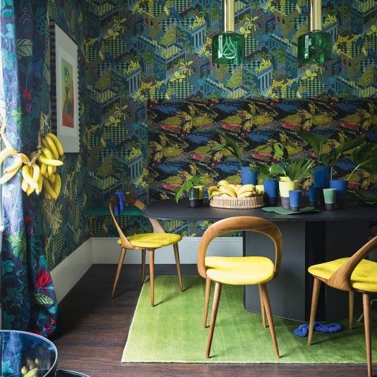 Go full-on tropical in a conversation-piece dining room with lush and vivid green and bright sunny banana yellow. An enchanting wallpaper and toning bench back rest create a no-holds-barred setting for a signature black dining table and designer chairs in eye-popping yellow