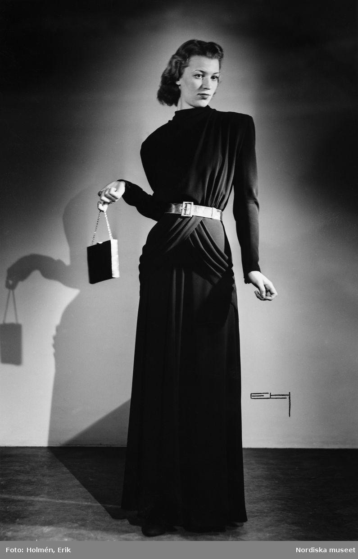 e46dac29cd80 Modell i svart, hellång aftonklänning med draperade detaljer och  silverskärp, aftonväska i handen. Foto: Erik Holmén