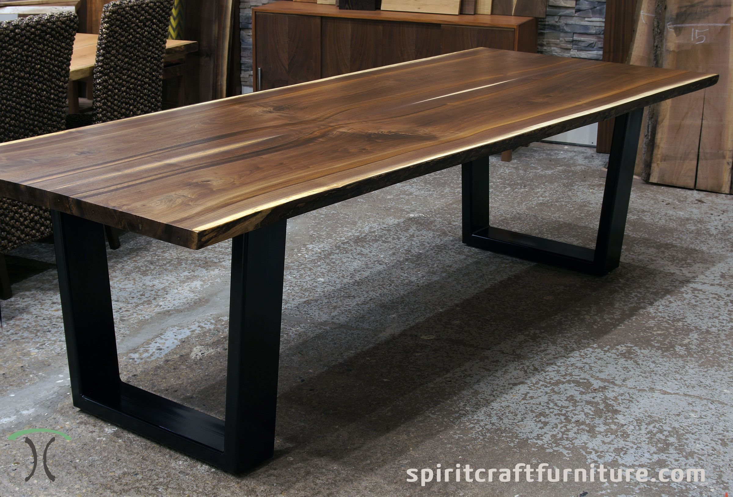 Black walnut live edge table with thick welded steel trapezoid legs handcrafted at chicago area furniture store