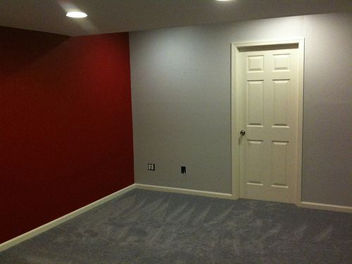 3 Grey Walls With One Red Accent Wall Baseboards Brown