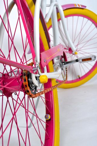 Fall in love all over again with bike riding! Our limited edition designer cruiser bicycle, Sorbet, is reminiscent of the joys of riding your bike with its vibrant color palette, refreshing pearl white frame, and multicolored pinstripe design. Everywhere you ride this bike, you will be sure to put a smile on people's faces with the color scheme - lemon yellow tires, magenta rims and tangerine chains!  Built by Villy Custom.     Women's Cruiser Bike, Sorbet, Bicyclette.com