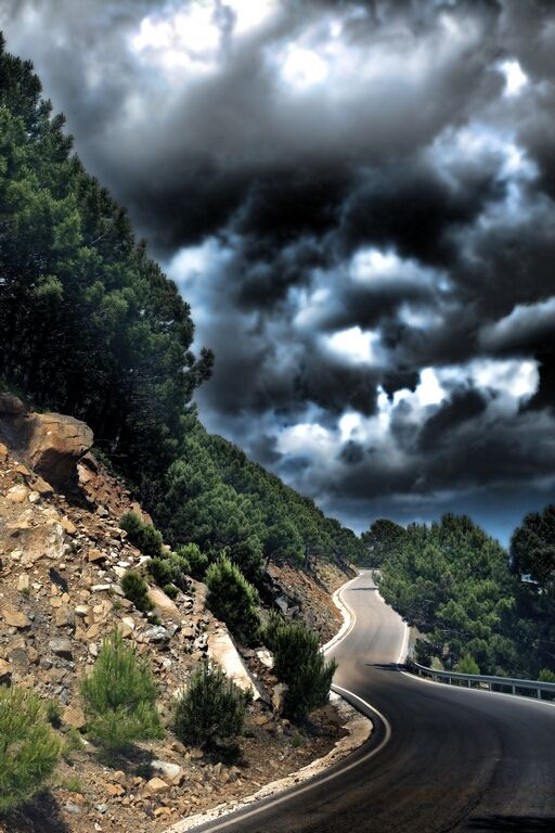 ominous clouds closing on the road