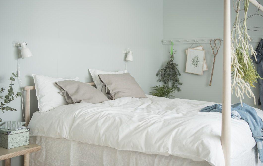 Symmetrisk soveværelse med grønne vægge, trægulve, grønne planter ...