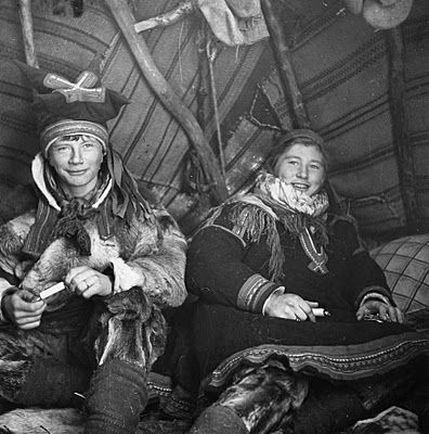 Sami children in a tent (lavvo) with traditional clothes from Kautokeino, Norway.