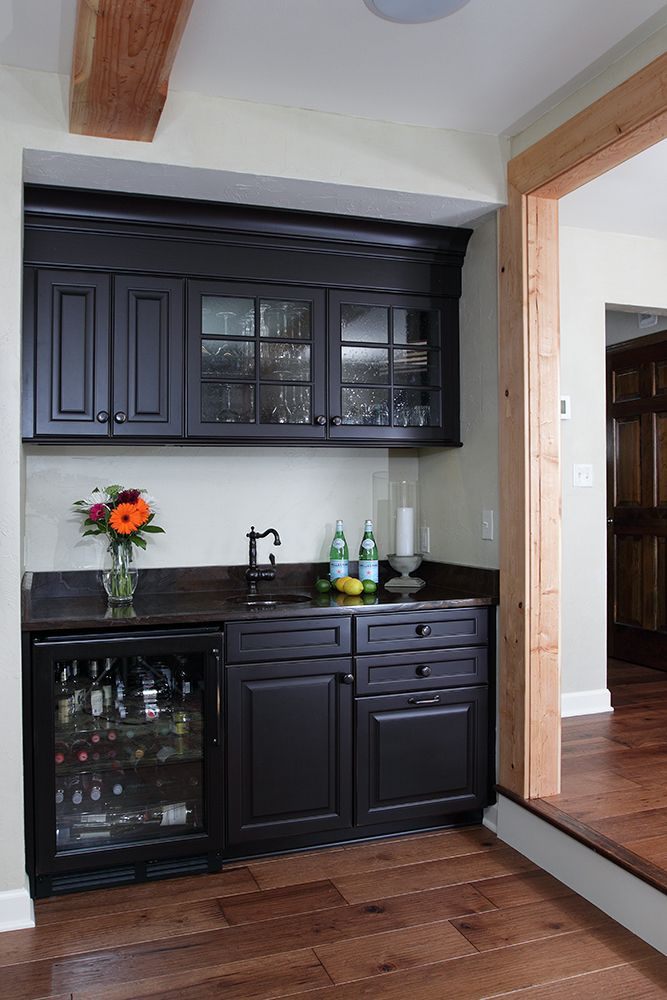 The wet bar includes custom cabinetry, a Bronzo Quartzite countertop ...