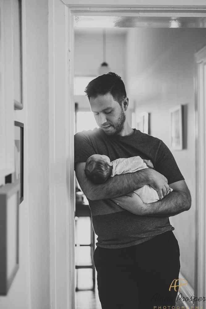 Black and white image of a father holding his new baby in the doorway during the...