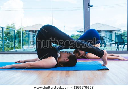 young woman doing headstand pose yoga interior fitness gym