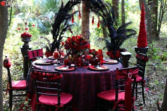 A Red Gothic Themed Wedding Table Setting With Giant Black Feathers