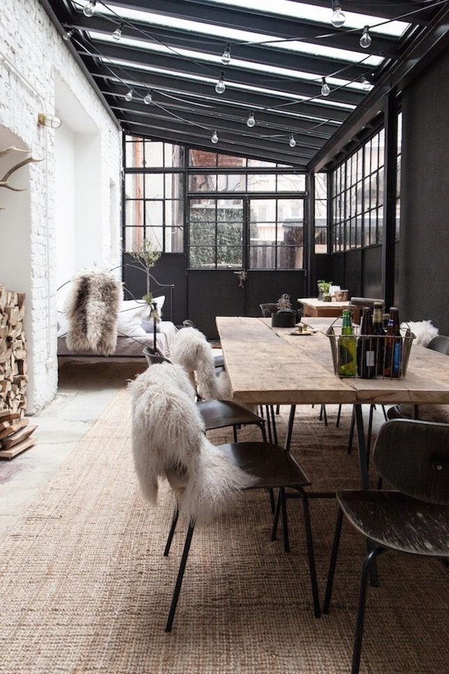 Perfect spot for a dining area | lots of natural light and cute string lights for when it's dark | the worn chairs and natural wood character along with the block wall add character and the black steel is a nice touch of contrast https://www.artisticsolutions.design/